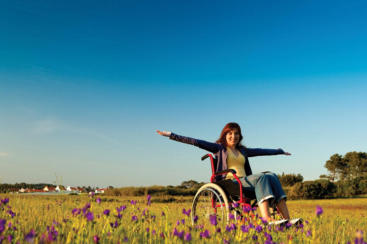 Woman in wheelchair flower field outdoors WEB RGB